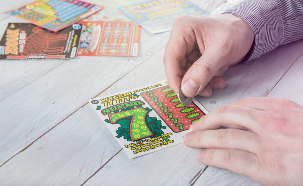 Man scratches lottery scratchcard.