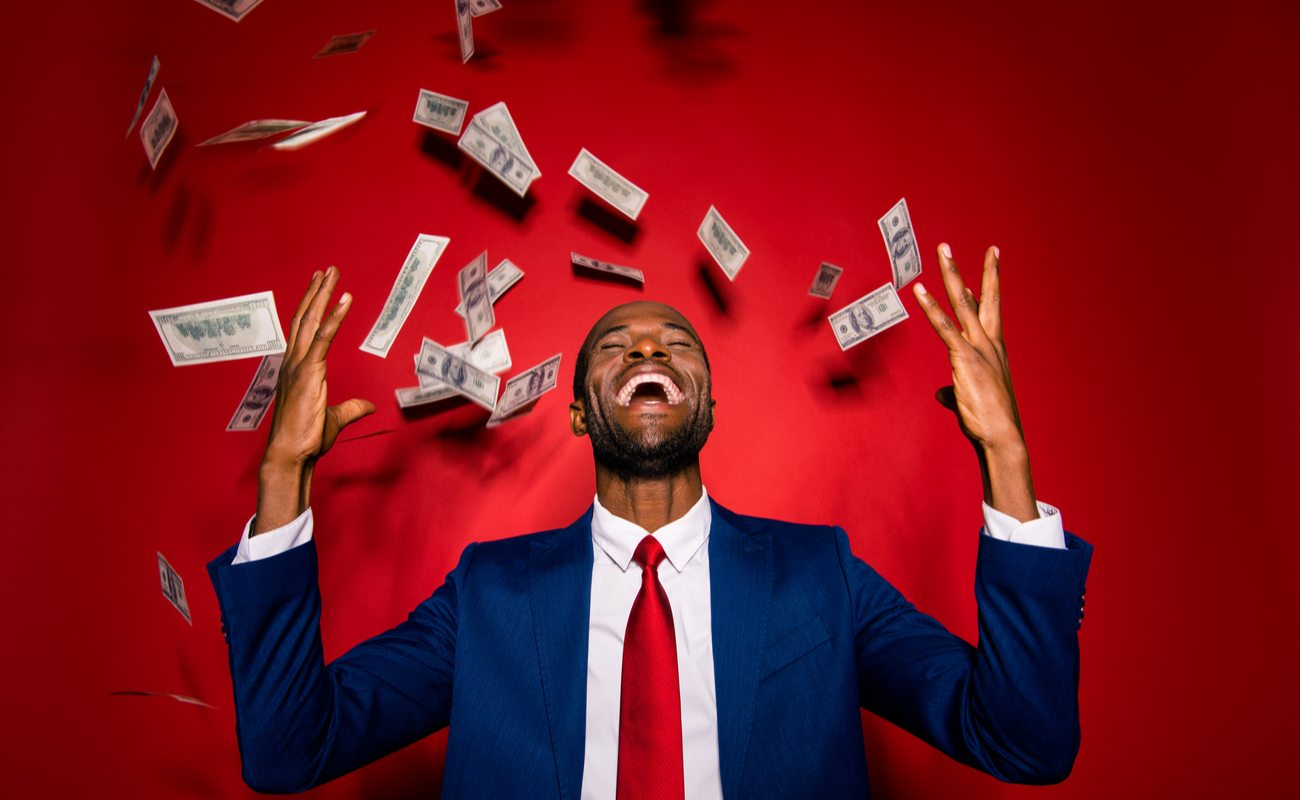 Man in blue suit and red tie laughs as money rains on him