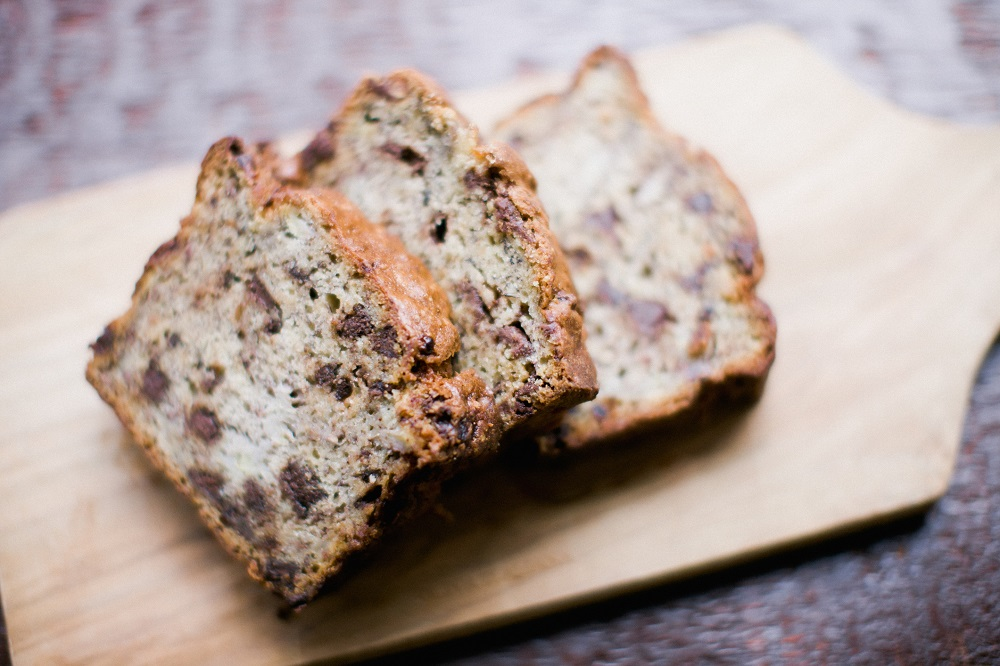 Chocolate chip banana bread on a wooden cutting board on a wooden table