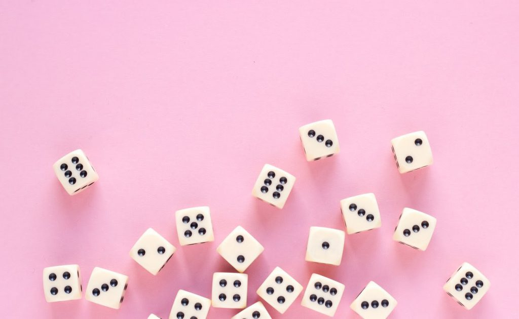 aming dice with copy space on pink background