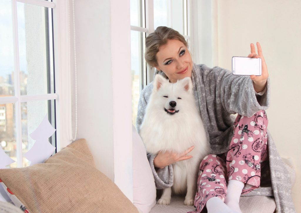 woman-taking-a-photo-of-herself-with-white-dog