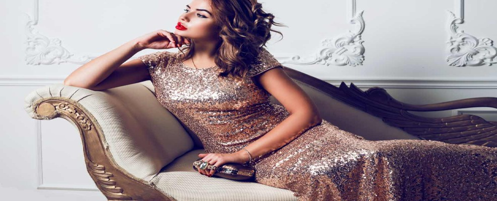 Beautiful lady in sequins dress sitting on luxury armchair, hollywood makeup.